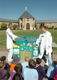 NCTC students Taryn Ogle (right) and Heatherly Meek (left) explain farm safety to kids at Immaculate Conception Catholic School during their health fair Wednesday April 24, 2013, in DentonAl Key - DRC