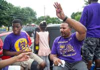 Broderick Kirksey waves from the Omega Psi Phi float in the Denton Juneteenth parade, which traveled from the Denton Civic Center to Fred Moore Park on Saturday morning.Matt Garnett - For the DRC