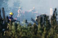 Ponder firefighters work to finish extinguishing a fire that started in a workshop on Odneal Rd, Tuesday, July 23, 2013, in Krum, TX.David Minton - DRC