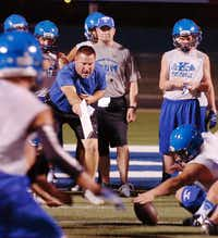 Krum head coach Gary Robinson (blue shirt) encourages his defense to go after a fumble during the first practice of the year just after midnight Monday August 5, 2013, in Krum, Tx.Al Key - DRC