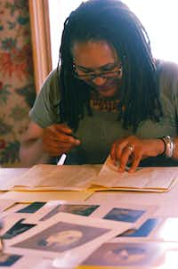 Joy Miller Davis looks over photos and letters from ancestors in the dining room of the Bayless-Selby House Museum on Wednesday in Denton.David Minton - DRC