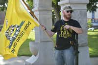 Ian McDougal holds a Gadsden flag as he and other open-carry advocates gather for a small rally Tuesday at the Denton County Confederate Soldier Memorial on the downtown Square.David Minton