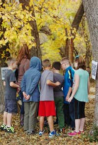 During 'Poetry in the Park' Butterfield Elementary School 3rd and 4th graders scanned in bar codes with their smartphones or tablets on trees, lightposts or anywhere they could find them at Porter Sports Complex Park in Sanger, for which they received a poem, written by a Butterfield student, that they read out loud to their class Thursday November 21, 2013. Photo by Al Key/DRC<252>Al Key