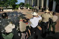 Members of the Denton County Sheriff's Office, Denton County constables, Texas Rangers and Texas Department of Public Safety troopers salute the flag during the Denton County Law Enforcement Officers Memorial Service on Wednesday in Denton.David Minton