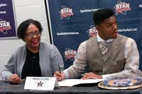 Ryan senior defensive end Sekou Clark signs a national letter of intent with Vanderbilt as his mother, Iris Clark, watches Wednesday in Denton.David Minton