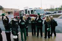 University of North Texas cheerleaders greet Santa as he arrives at Golden Triangle Mall in a fire engine Saturday in Denton.David Minton - DRC