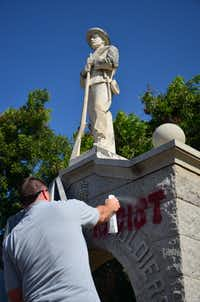 "A worker sprays solution on graffiti on the Confederate soldier memorial outside the Courthouse on the Square. The words ""This is racist"" were spray-painted on the monument late Sunday or early Monday.Caitlyn Jones - DRC"
