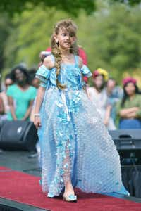 "Briana McBeain, 8, goes down the runway in a dress inspired by the movie ""Frozen"" during the Trashion Show at Saturday's Redbud Festival. The garment was fashioned from bubble wrap and blue plastic.David Minton - DRC"