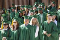 University of North Texas graduates wave to family and friends in the stands as they enter the field at Apogee Stadium during Friday's university-wide commencement ceremony.David Minton