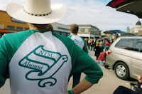 "Some UNT alumni show their school pride by wearing shirts bearing the so-called ""Flying Worm,"" the eagle logo used by the university in the 1970s, during Saturday's homecoming parade in downtown Denton.David Minton - DRC"