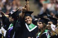 Graduates point to their families in the crowd to thank them Saturday at the UNT Coliseum.David Minton - DRC
