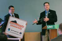 Meteorologist Mark Fox gives a sign to Andrew Harris, University of North Texas vice president for finance and administration, during a press conference Thursday in Denton.David Minton - DRC