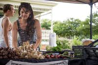 Employee Sarah Schulwitz tidies up the Johnson's Backyard Garden stand at the Denton Community Market on June 14. The business sells locally grown produce on Saturdays at the market, which sets up at the Historical Park of Denton County.Matt Garnett