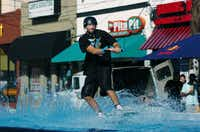 A wakeboarder heads toward the jump ramp past restaurants and bars on Avenue A. Wakepoolooza was was a daylong event staged to promote the sport of cable wakeboarding.David Minton - DRC