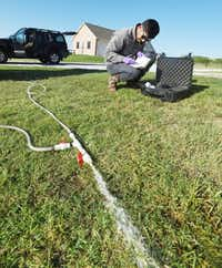 University of Texas at Arlington biochemist Zacariah Hildenbrand logs data from a water sample from a well at a home on Amyx Ranch Drive near Ponder recently.Al Key - DRC