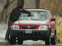 Travis Lowe scrapes ice off his vehicle on Oaklawn Avenue during the sleet storm Sunday March 2, 2014, in Denton.Al Key - DRC