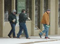 DATCU employees David Candioto, left, and Rusty Thompson, middle, put de-icer around the front door and sweet the snow off the sidewalk for customers during the snowstorm Thursday morning on Mulberry Street.Al Key - DRC