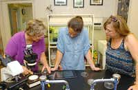 North Central Texas College biology professor Lisa Bellows, left, helps Tiffany Schmitz, a Houston YES Prep teacher, and Sharon Sanders, a Sanger Middle School teacher, see plankton through the microscope via their iPads during teacher training at the school Thursday in Gainesville.Al Key - DRC