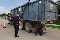 Denton Police officers Tom Birckbichler, left, and Scott Burson, under truck, inspect a truck near the intersection of the Sam Rayburn Tollway and Marchant Boulevard Wednesday June 5, 2013, in Carrollton.Al Key - DRC