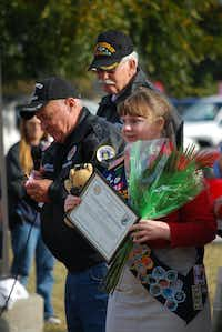 Lydia Bishop, 17, is given a plaque and a bouquet of roses by the Vietnam Veterans of America for her efforts in helping start and organize the first Veterans Day Parade in Lake Dallas on Sunday.John D. Harden - DRC