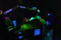 A worker uses fluorescent dye to test for defects of parts for aircraft landing gear at Mayday Manufacturing on Thursday, Dec. 12, in Denton.David Minton - DRC