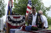 Wayne Trevathan, commander of Veterans of Foreign Wars Post 2205, salutes a flag placed during a Memorial Day service Sunday at Roselawn Memorial Park.Bj Lewis