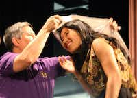 Denton High School senior Rebecca Fu ducks underneath as Donald Place, student adviser for the school's National Honor Society chapter, places an NHS shawl over her head during Denton High's recent senior awards assembly.Mario Zavala, Denton ISD - Courtesy photo