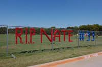 Plastic cups in a chain-link fence spell out a message to honor Guyer High School senior football player Nathan Maki at Guyer High School in Denton. More coverage, pages 8A and 1B.David Minton