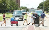 Anjelika Cortez, left, an incoming freshman at Texas Woman's University, gets help moving into the dorm from her mom Annette, second from left, her brother Joey, second from right, and her father Hernan, right, as they cross Bell Avenue to go to Stark Hall on Wednesda.Al Key