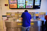 An employee works at the new Which Wich at TWU on Friday in Denton.David Minton