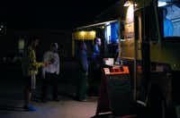 Customers wait in line to order from The Waffle Wagon, parked in front of East Side Social Club on Thursday in Denton.David Minton - DRC
