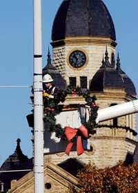 A DME employee puts Christmas wreaths on the light posts around the Courthouse-on-the-Square recently. Wednesday November 30, 2011, in Denton.Al Key - DRC