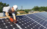 Brandon Karakashevich, an employee of Glean Power, a Denton solar and wind power company, installs solar panels on a Habitat for Humanity house on Lakey Street on May 13.Al Key - DRC
