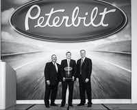 Eddy Stahl, center, dealer principal and president of Stahl Peterbilt-Edmonton, accepts the dealer of the year award from Robert Woodall, left, Peterbilt director of sales and marketing, and Bill Kozek, Peterbilt general manager and PACCAR vice president.
