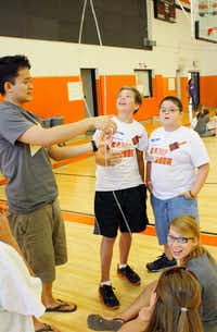 Daniel Kee, a volunteer from The Village Church, assists seventh-grader Seth Herrman, left, and sixth-grader Tyler Smith while Victoria Whitmore describes the project to other students.Mario Zavala