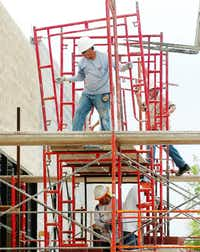 Construction workers assemble scaffolding as they build a new location for the Wash Factory on West University Drive on Friday in Denton.Al Key - DRC