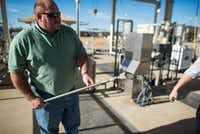 John Bennett, plant manager of the Denton Creek Regional Wastewater System in Roanoke, demonstrates a tool used to collect samples of the water as it goes from effluent to clean, reusable water through the system.Robert Yu - For the DRC