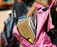 A school supply kit fills a backpack at the Apple Tree Project  distribution day in 2010.DRC file photo