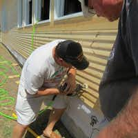 Gary Steele works with a nail gun to attach new siding to the Green Valley School building, which was constructed in 1919.Courtesy photo