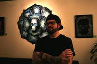 "Robert Hamilton, a Carrollton artist and a University of North Texas graduate, stands in front of one of his new creations, ""Blue flower and sugar skull,"" at Wine2 on Thursday in Denton. Hamilton's style — bright colors and loose lines inspired by tattoos and by Dia De Los Muertos folk art — established the aesthetic of Denton's Day of the Dead Festival. <137>The exhibit at the local wine shop is the official beginning of Denton's Day of the Dead for the artist.<137>Lucinda Breeding"