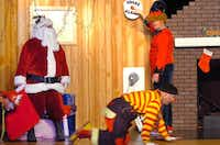 Buddy (Shane Robert), right, tests a smoke alarm with Santa Claus (Chris Johnson), prompting Booster (Charlie Schenck), right bottom, to crawl toward the door with Flash (Hank Morrow) on their way out of the possibly burning house during a performance of the Denton Fire Department's Clowns on Fire at Nelson Elementary School on Thursday in Denton.Al Key