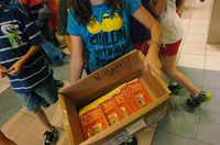 "A student holds a box containing copies of ""The World According to Humphrey"" for her class at Ponder Elementary School on Tuesday.David Minton"