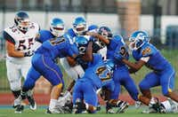 Ryan senior running back Tyrone Williams (6) is brought down by a pack of Corsicana defenders, Friday, August 30, 2013, at Tiger Stadium in Corsicana.David Minton
