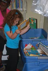 Skylar Seidel, 3, digs through a bin of children's books at the Lake Cities Library on Thursday.John D. Harden