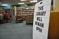 "Lake Cities Library officials placed a sign that reads ""This library will remain open"" in response to the City of Corinth voting to cut and eventually pull funding from the library.John D. Harden"
