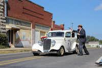 Jonathan Davis, acting as sheriff, shoots at the direction of the Farmers and Merchant Bank Building during the bank robbery re-enactment Saturday afternoon for Bonnie and Clyde Days in downtown Pilot Point.Megan Gray