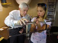"Clarence ""Woody"" Wood shows Abby Geiseke the custom modified flute and stand which allows her to play with one hand<252>"