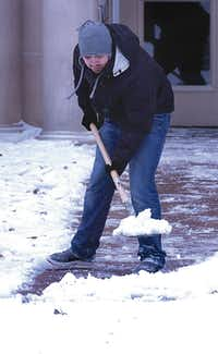 T.J. Zambrano shovels snow off the sidewalk in front of Clark Hall at the University of North Texas after Tuesday's winter storm.