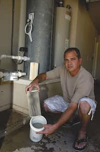 In June, Damon Smith shows the dirty water filter he changed just five days ago at his home in Dish. Smith said his wife, Amber, first noticed the water's gray appearance in March 2009 after a gas well was drilled near the family's home. Early testing of the Smiths' well water found levels of arsenic, lead and chromium unsafe to drink. Subsequent tests found lower levels of contamination.