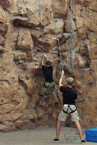 Craig Cornish, right, spots Evan McLemee on the climbing wall Friday   in Texas Woman's University's Fitness and Recreation Center. The two   students, who work at the center, were demonstrating the climbing wall   during the grand opening of the new facility.